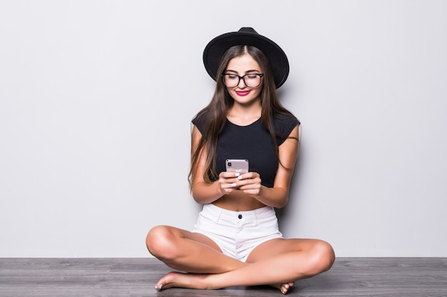 Smiling woman in black hat sitting on the floor and using smartphone isolated over gray background