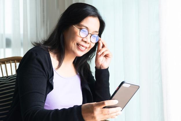 웃는 여자 검은 긴 머리 앉아 스마트 폰을 들고 가족과 의사 소통