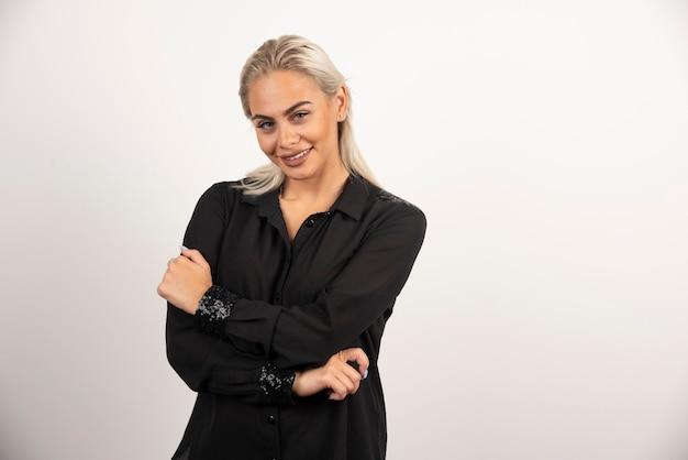 Donna sorridente in camicia nera in posa su sfondo bianco. foto di alta qualità