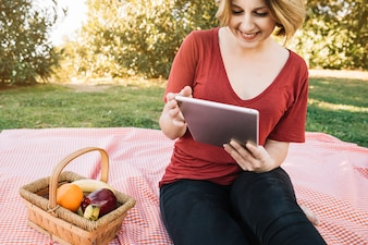 Smiling woman browsing tablet on picnic