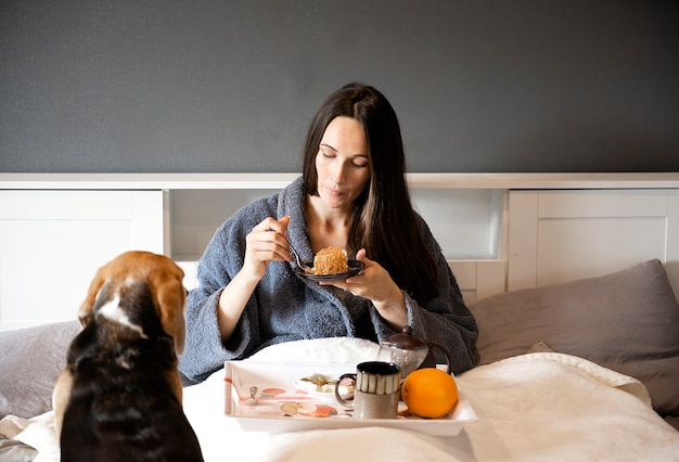 Улыбающаяся брюнетка женщина ест торт для завтрака и пьет горячий чай в постели у себя дома