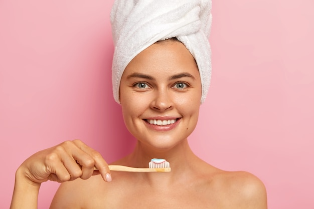 Smiling woman brushes teeth with toothpaste holds wooden toothbrush, wears towel on head, enjoys hygienic procedures