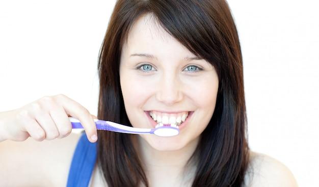 Smiling woman brushing her teeth