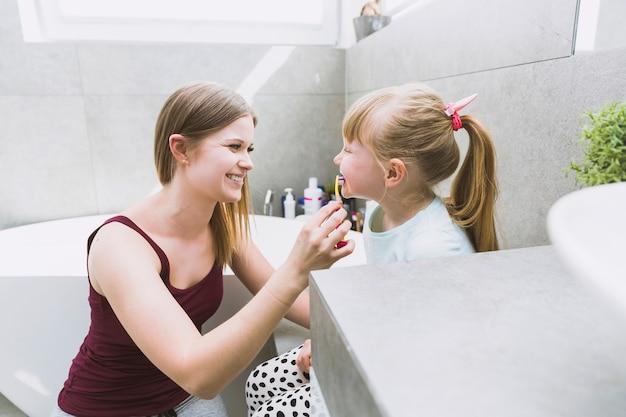Smiling woman brushing teeth of daughter