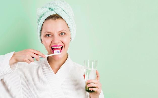 Улыбающаяся женщина, чистящая зубы зубной пастой и зубной щеткой в ванной комнате. стоматологическая гигиена. чистка зубов.