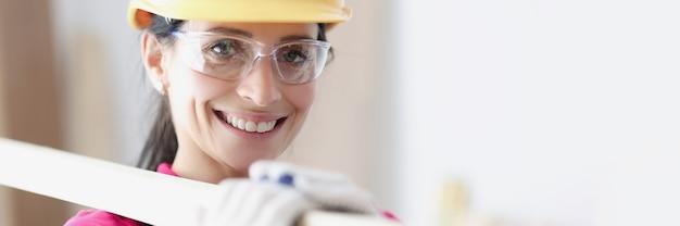 Smiling woman builder in helmet holds building materials