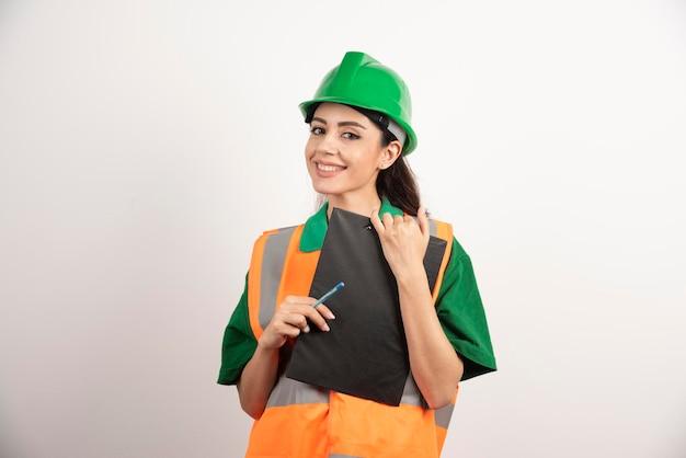 Усмехаясь построитель женщины держа доску сзажимом для бумаги на белой предпосылке. фото высокого качества