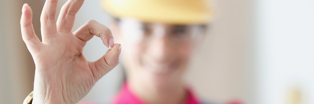 Smiling woman builder holds thumbs up in gesture ok