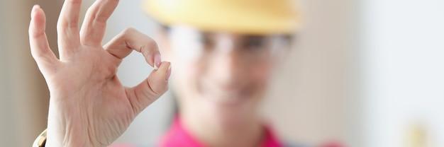 笑顔の女性ビルダーはジェスチャーで親指を立てます