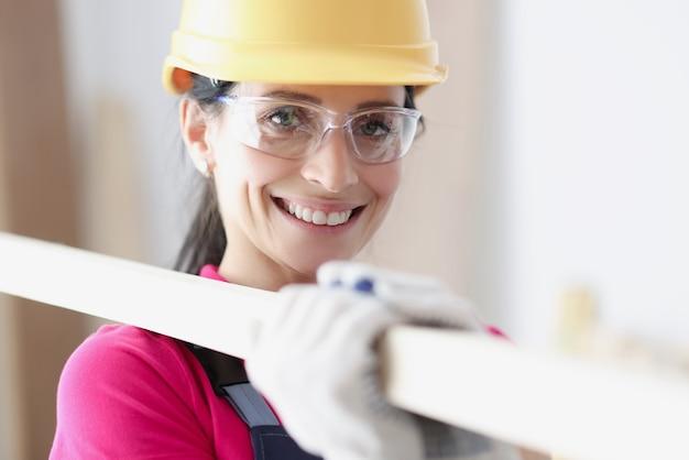 Улыбающаяся женщина-строитель в шлеме держит строительные материалы