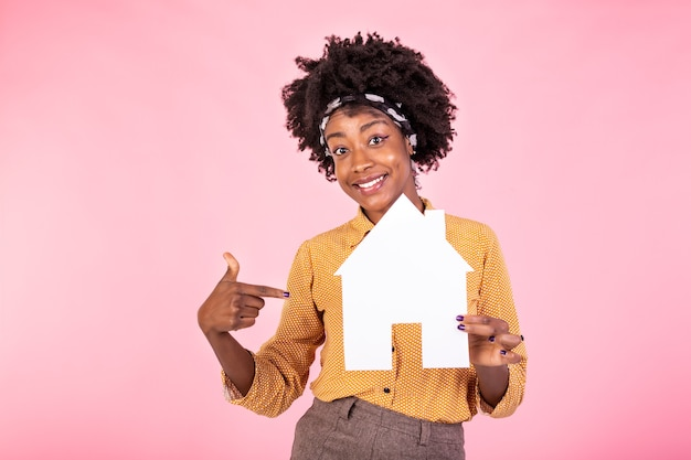 Smiling  woman buying home, holding paper house in hands and smiling, paying debt, standing white background happy