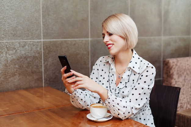 Smiling woman in cafe looking at smartphone