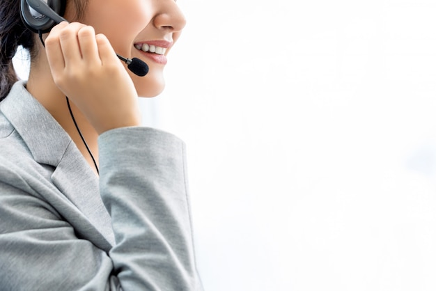 Smiling woman call center staff on white wall with copy space