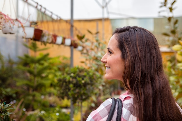 Smiling woman carrying bag in greenhouse