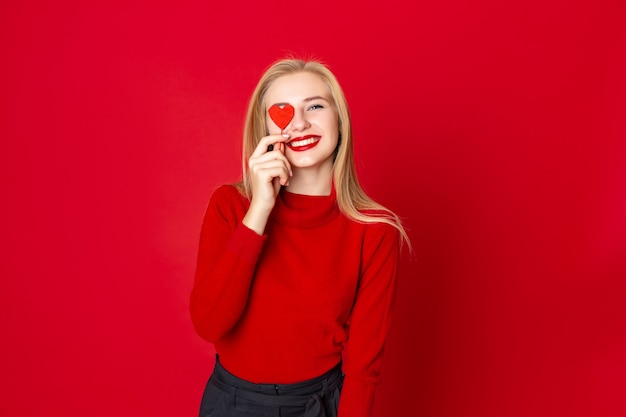 Smiling woman in casual sweater over red background