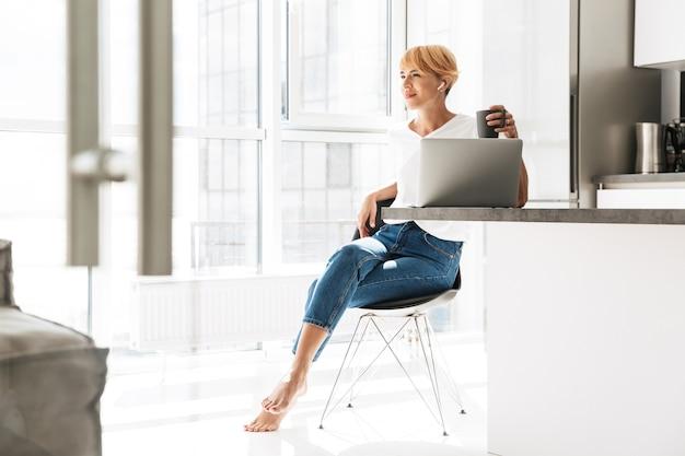 キッチンに座って、イヤホンを身に着けている間ラップトップコンピューターを使用してカジュアルな服を着た笑顔の女性