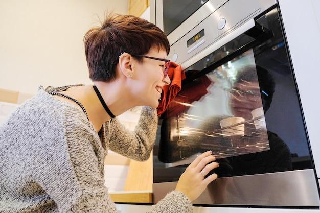 Улыбающаяся женщина проверяет готовность выпечки в духовке