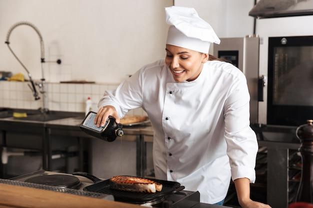 웃는 여자 요리사 요리사 유니폼 요리 맛있는 연어 스테이크 서 부엌에서 올리브 기름을 붓는 입고