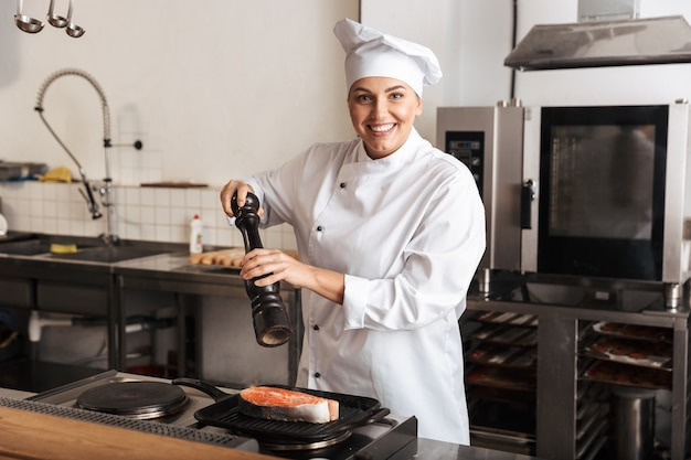 부엌에서 서있는 맛있는 연어 스테이크를 요리하는 유니폼을 입고 웃는 여자 요리사 요리사