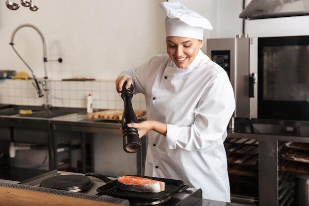 Улыбающаяся женщина-шеф-повар в униформе готовит вкусный стейк из лосося, стоя на кухне