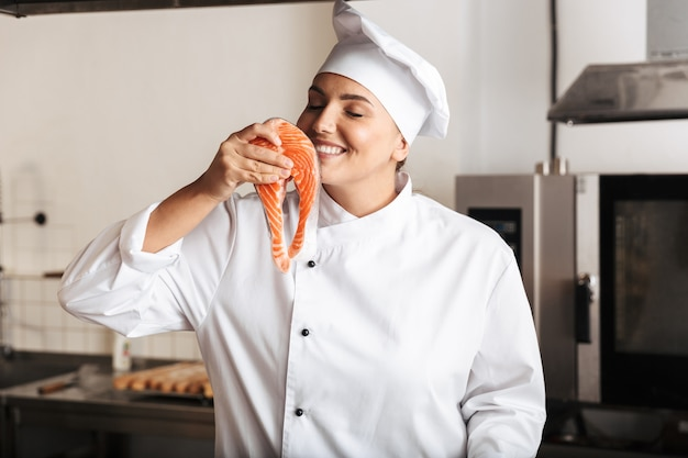 Smiling woman chef cook wearing uniform cooking delicious salmon steak standing at the kitchen