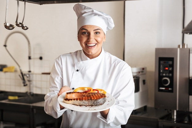 Smiling woman chef cook wearing uniform showing cooked grilled salmon steak while standing at the kitchen