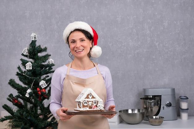 サンタの帽子をかぶった笑顔の女性シェフがジンジャーブレッドハウスを手にしています。クリスマスの飾り。