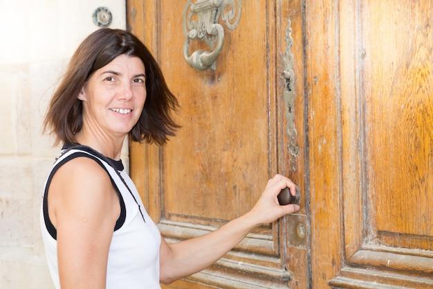 Smiling woman in city street open building apartment door