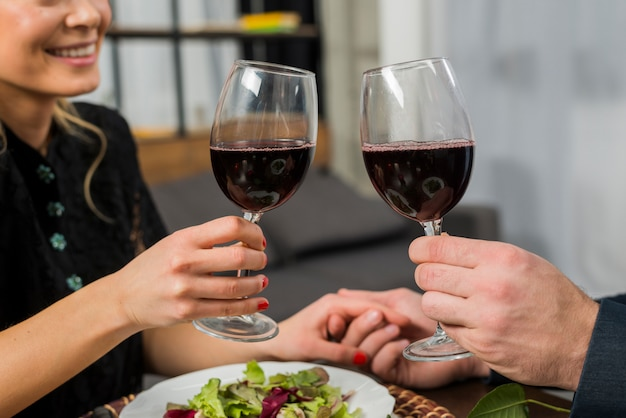 Smiling woman clanging glasses of wine with man at table