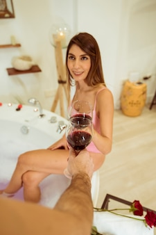 Smiling woman clanging glasses with man near roses and spa tub with water