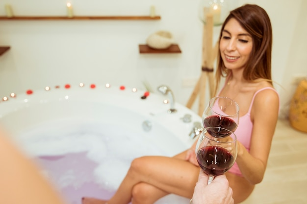 Smiling woman clanging glasses with person near spa tub with water