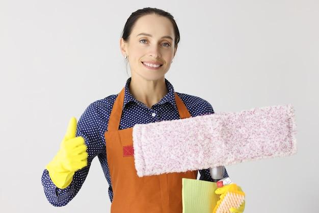 웃는 여성 청소부는 사무실을 위한 청소 회사의 서비스를 엄지손가락으로 들고 있습니다.