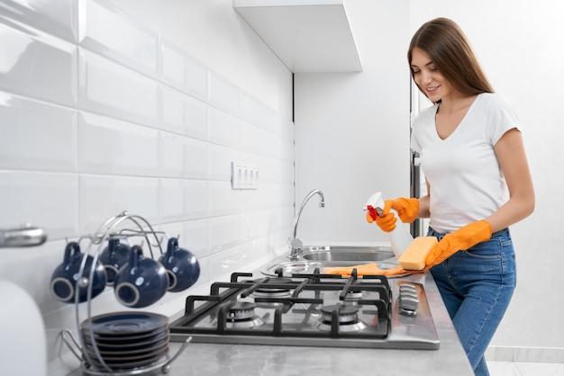 Улыбающаяся женщина чистит умывальник и плиту
