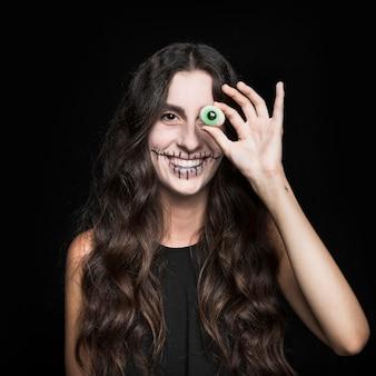 Smiling woman closing eye by fake blinker