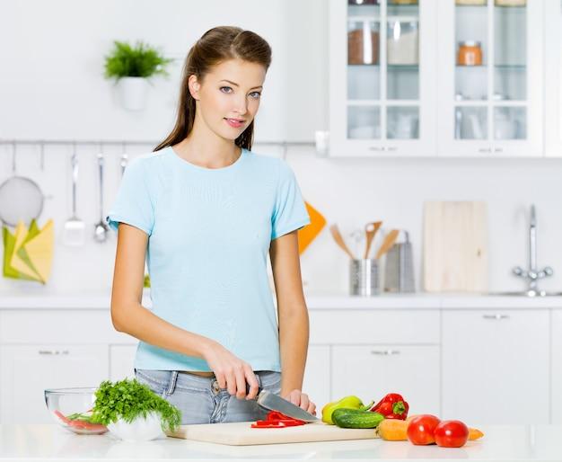 Улыбающаяся женщина готовит здоровую пищу на кухне