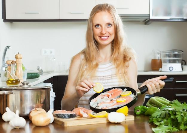 Улыбается женщина приготовления лосося с лимоном
