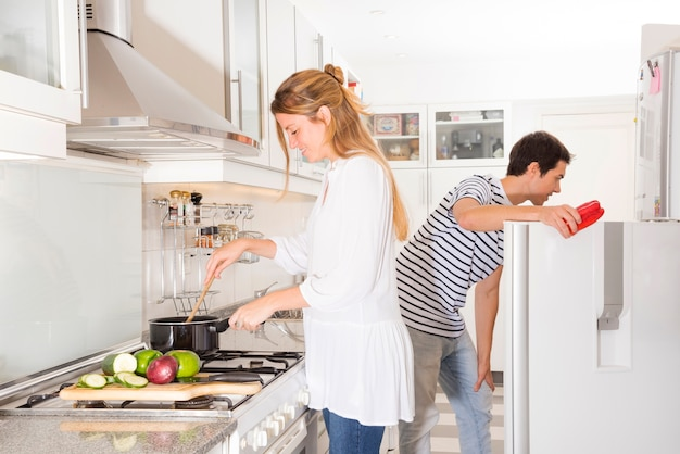 Smiling woman cooking vegetables while her husband opening the refrigerator door