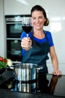 ストーブの上に鍋で野菜を調理し、赤ワインを飲む女性の笑みを浮かべてください。