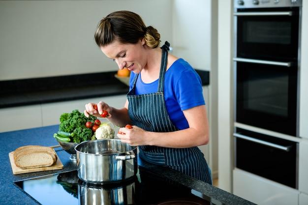 ストーブの上に鍋で野菜を調理笑顔の女性