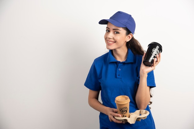 コーヒーを 2 杯入れた笑顔の女性宅配便。高品質の写真