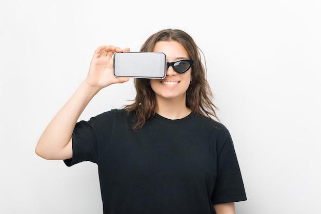 Улыбающаяся женщина закрывает один глаз своим телефоном, стоя на белом фоне.