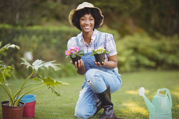 Smiling woman crouching in the garden holding flowers