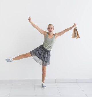 環境にやさしい買い物袋とクレジットカードで踊る笑顔の女性