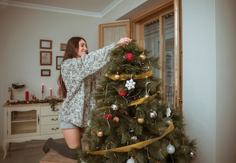 Smiling woman decorating Christmas tree in living room