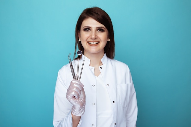 Smiling woman dentist holding in hands instruments.