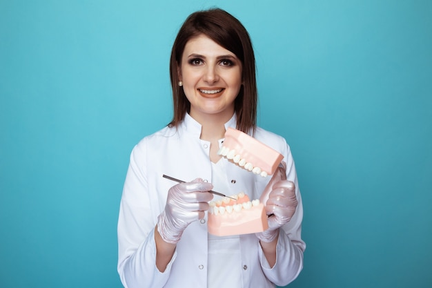 Smiling woman dentist holding in hands model of jaw and instruments.