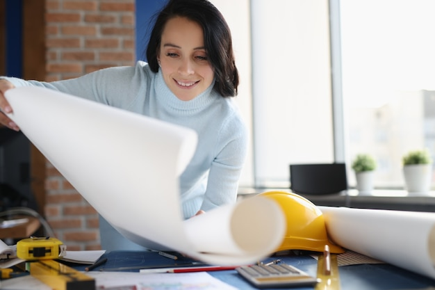 Smiling woman designer in her office development of design of apartments and houses concept