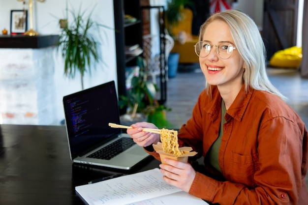 Smiling woman developer eating asian noodles in home office