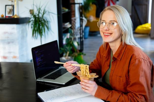 홈 오피스에서 아시아 국수를 먹는 웃는 여성 개발자