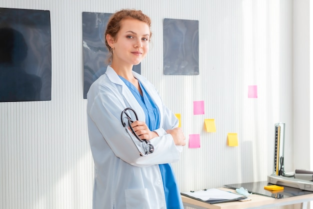 Smiling woman doctor possing and wearing a stethoscope on hospital room.